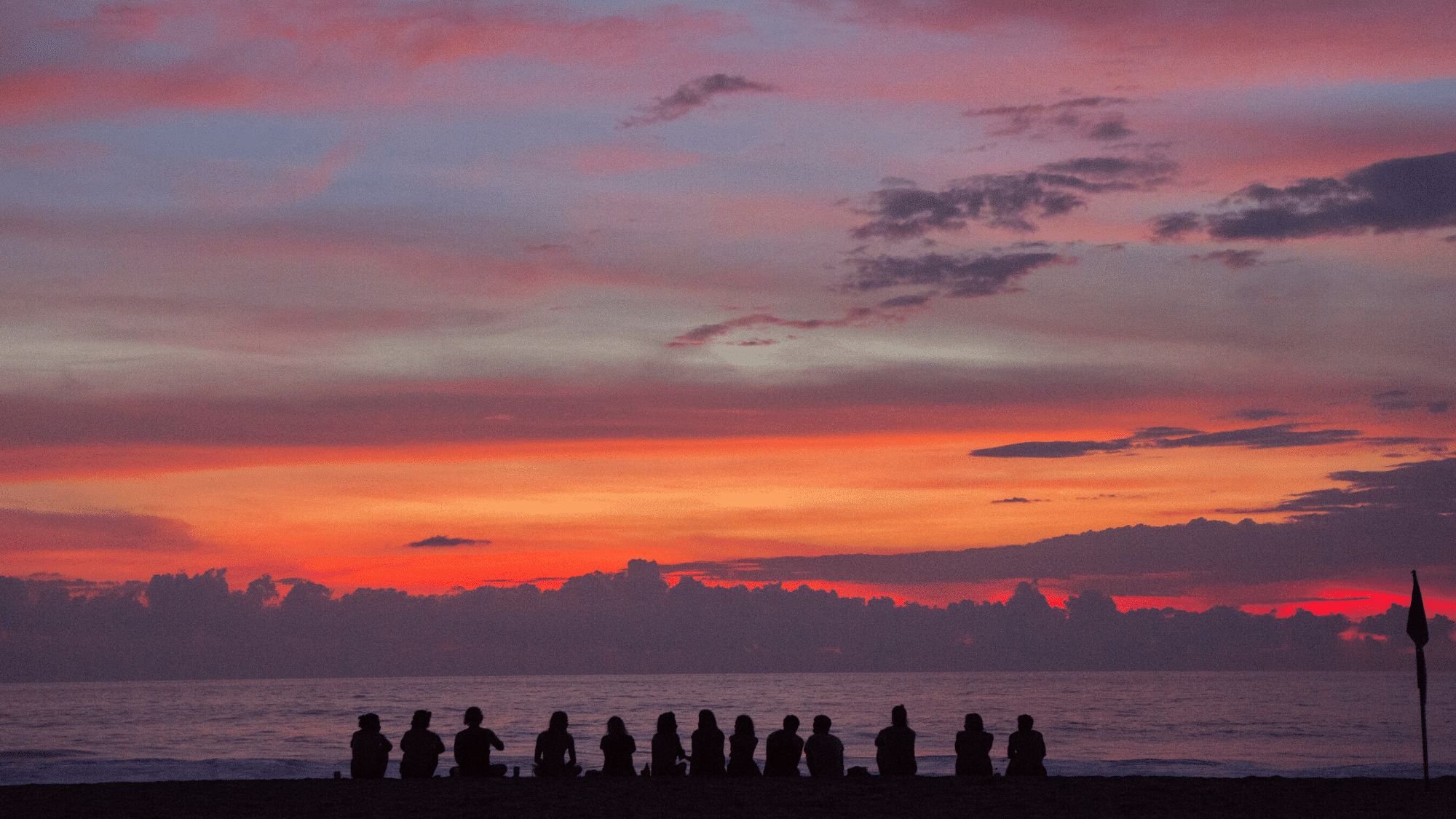 Group of people on the beach watching the sunset