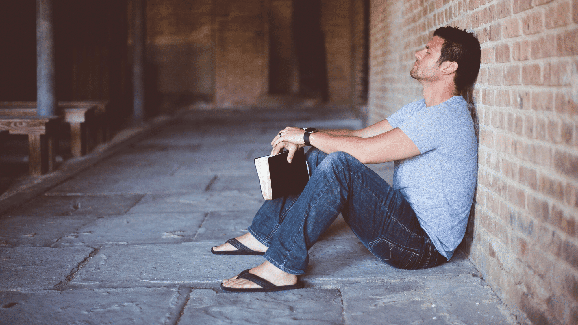 A man with a book is sitting on the ground with a closed eyes